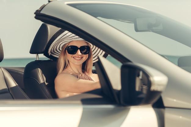 La giovane donna guida un'automobile sulla spiaggia