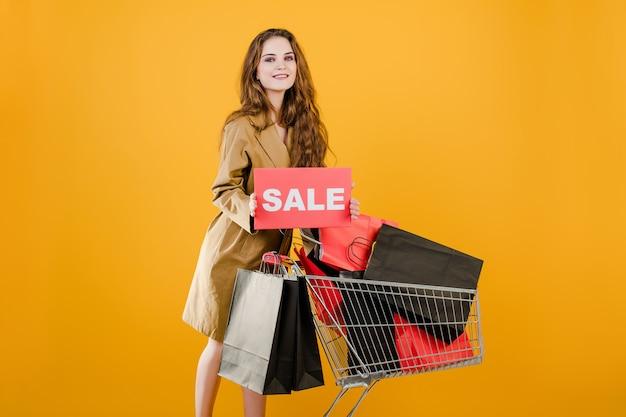 La giovane donna ha il segno di vendita con il carrello pieno dei sacchetti della spesa isolati sopra giallo