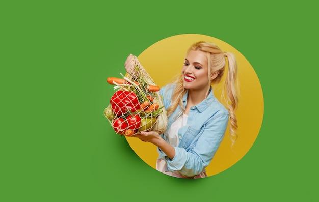 La giovane donna ha raccolto gli ortaggi freschi in un sacchetto di stringa su una priorità bassa verde. sbircia da un buco rotondo nel muro.