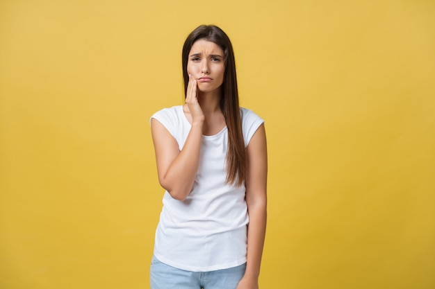 La giovane donna ha un mal di denti, foto dello studio isolata su una priorità bassa gialla