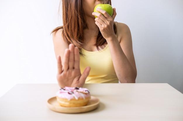 La giovane donna in buona salute che per mezzo della mano spinge dessert e dolci e sceglie la mela verde