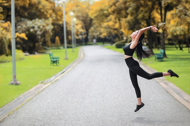 La giovane donna in buona salute e sportiva fa l'allungamento di yoga all'aperto