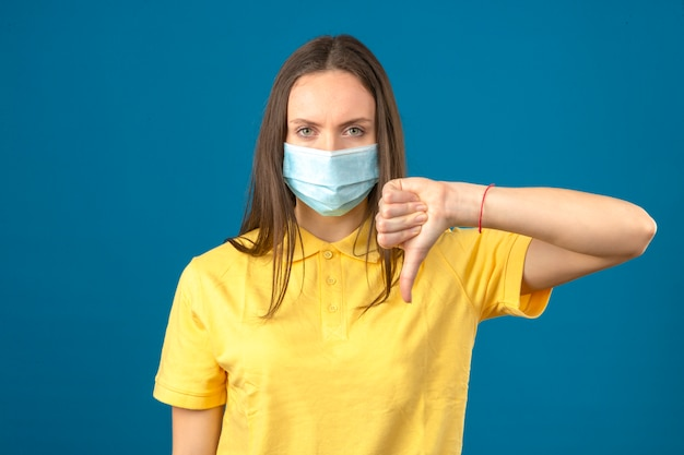 La giovane donna in camicia di polo gialla e maschera protettiva medica che fa i pollici giù firma seriamente l'esame della macchina fotografica sul fondo blu isolato