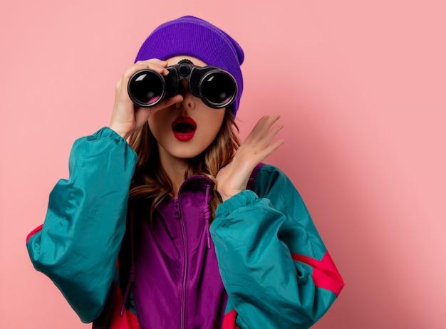 La giovane donna in cappello viola e gli anni 90 copre con i bonocoli sulla parete rosa