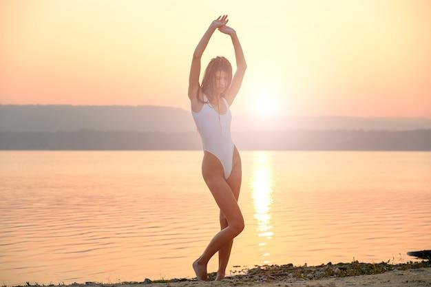 La giovane donna in costume da bagno delle stringhe sta sulla spiaggia nell'alba