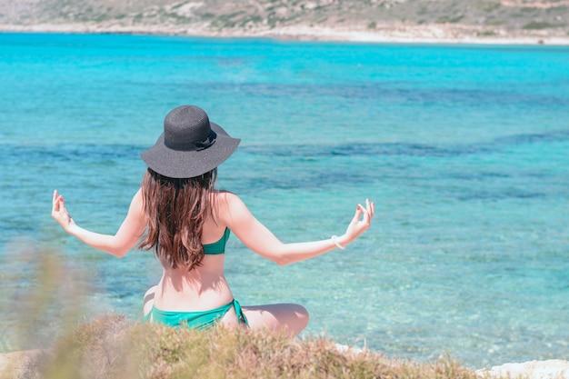 La giovane donna in costume da bagno verde e black hat pratica lo yoga sulla spiaggia del mar mediterraneo.