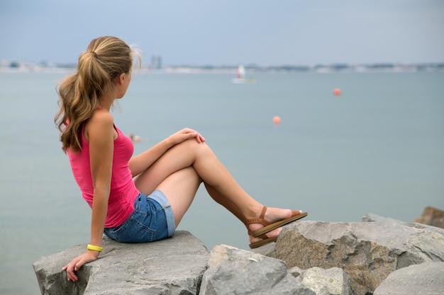 La giovane donna in estate copre la seduta sui grandi massi sul puntello di mare che osserva sull'orizzonte.