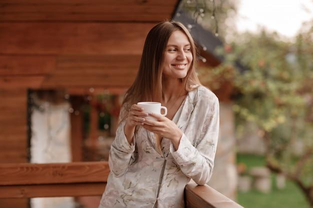 La giovane donna in indumenti da notte alla moda gode di di bere il caffè