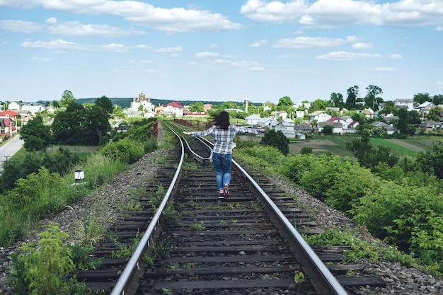 La giovane donna in jeans e camicia corre lungo la strada ferrata