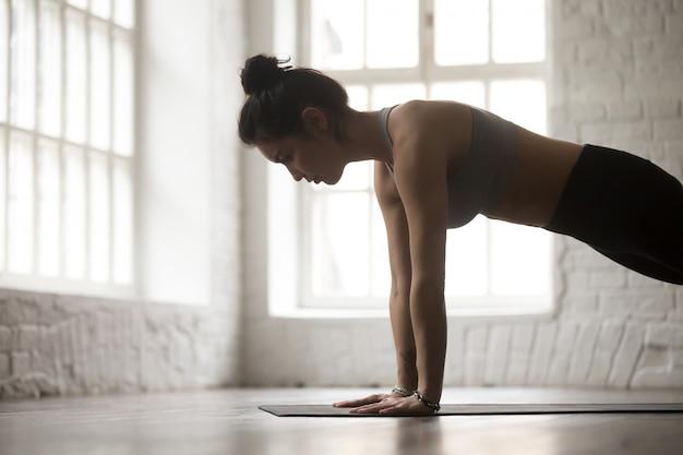 La giovane donna in spinge aumenta o preme la posa, primo piano