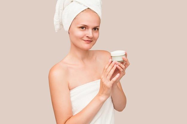 La giovane donna in tovagliolo bianco applica la crema idratante