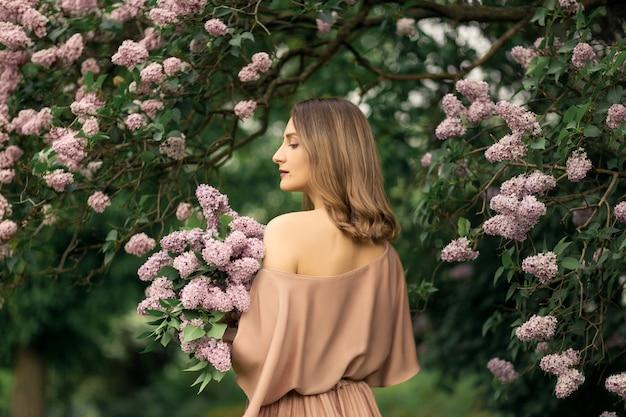 La giovane donna in un bel vestito è in piedi vicino a un cespuglio lilla