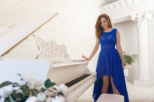 La giovane donna in un vestito blu sta stando vicino ad un piano bianco e guarda giù