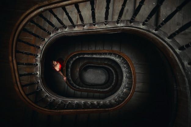 La giovane donna in un vestito rosso scende le scale di legno vorticose.
