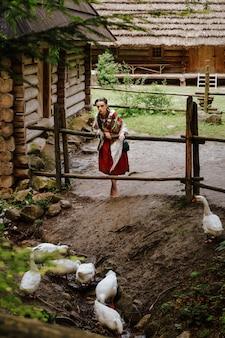 La giovane donna in un vestito tradizionale ucraino sta camminando nel cortile e sta alimentando le oche