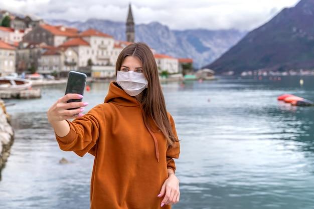 La giovane donna in una mascherina medica prende un selfie sulla via di una città europea.