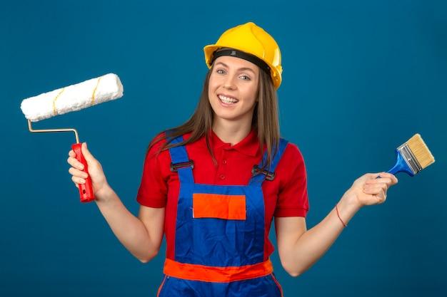 La giovane donna in uniforme da costruzione e casco di sicurezza giallo sorridenti che tengono il rullo e la spazzola di pittura in mani che stanno sul fondo isolato blu