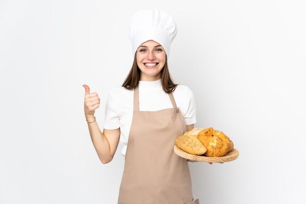 La giovane donna in uniforme del cuoco unico isolata su bianco dando pollici aumenta il gesto