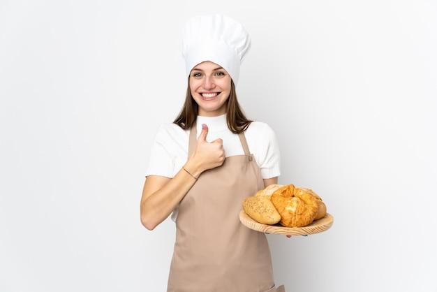 La giovane donna in uniforme del cuoco unico sulla parete bianca che dà pollici aumenta il gesto