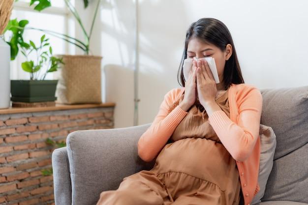 La giovane donna incinta asiatica soffre di influenza e starnuti, naso che cola, naso chiuso e poi soffiarsi il naso usando un fazzoletto