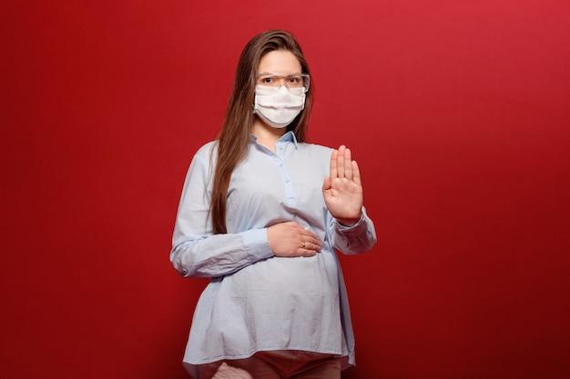 La giovane donna incinta sulla parete rossa nella mascherina medica protettiva tiene sullo stomaco