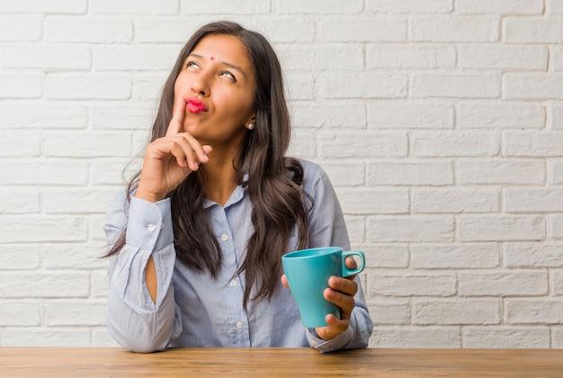 La giovane donna indiana che pensa e guarda su, confusa su un'idea, starebbe cercando di trovare una soluzione
