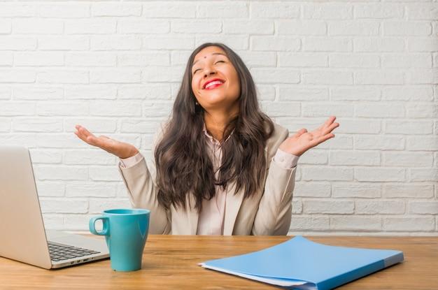 La giovane donna indiana in ufficio ridendo e divertendosi, essendo rilassata e allegra, si sente sicura e di successo