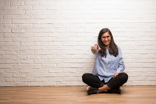 La giovane donna indiana si siede contro un muro di mattoni allegro e sorridente che indica la parte anteriore