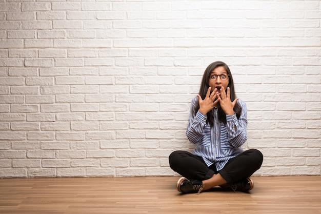 La giovane donna indiana si siede contro un muro di mattoni sorpreso e scioccato, guardando con gli occhi spalancati, eccitato da un'offerta o da un nuovo lavoro, concetto di vittoria