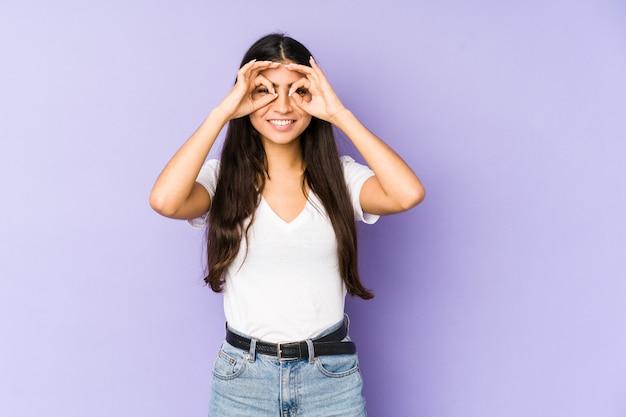 La giovane donna indiana sulla parete viola ha eccitato mantenendo il gesto giusto sull'occhio.