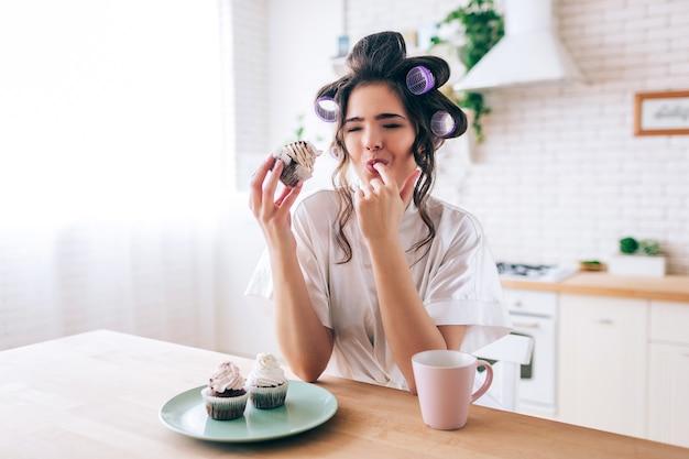 La giovane donna infelice turbata mangia i pancake con crema sulla cima. dito che perde. tazza e frittelle sul tavolo. solo in cucina. luce del mattino.