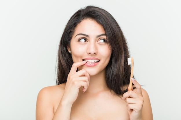 La giovane donna ispanica che tiene uno spazzolino da denti si è distesa pensando a qualcosa che esamina uno spazio della copia.