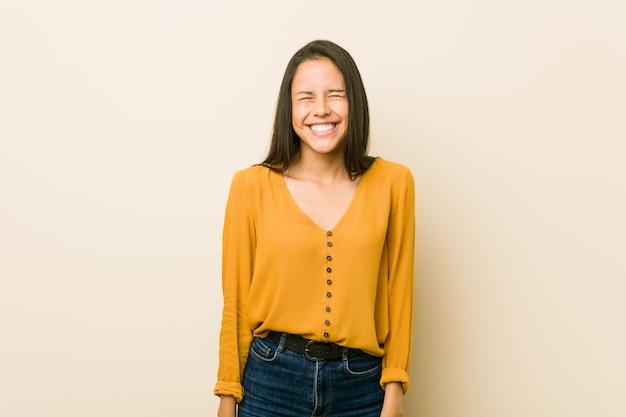 La giovane donna ispanica contro una parete beige ride e chiude gli occhi, si sente rilassata e felice.