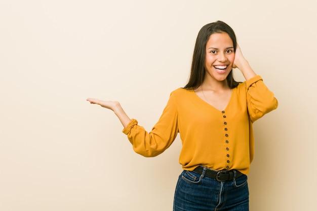 La giovane donna ispanica contro una parete beige tiene lo spazio della copia su una palma, tiene la mano sulla guancia. stupito e felice.