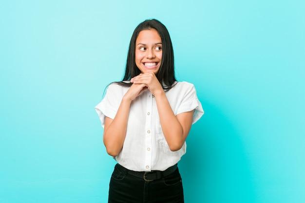 La giovane donna ispanica fresca contro una parete blu tiene le mani sotto il mento, sta guardando felicemente da parte.