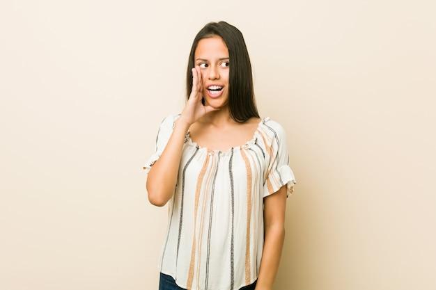La giovane donna ispanica sta dicendo una notizia di frenata calda segreta e sta guardando da parte