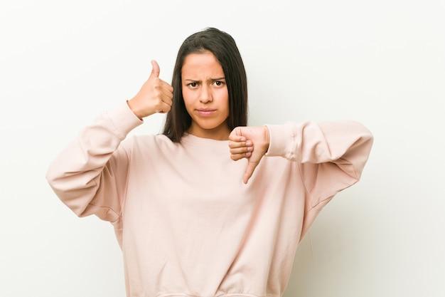 La giovane donna ispanica sveglia dell'adolescente che mostra i pollici su e pollici giù, difficile sceglie il concetto