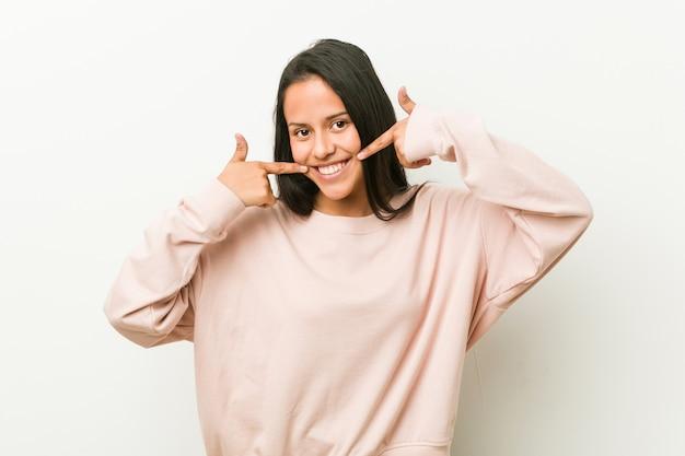 La giovane donna ispanica sveglia dell'adolescente sorride, indicando le dita alla bocca.