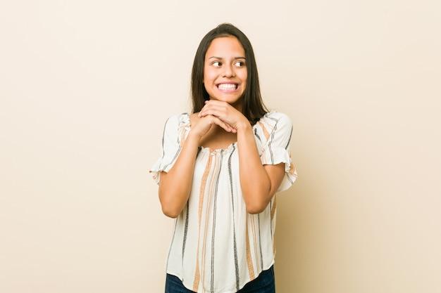 La giovane donna ispanica tiene le mani sotto il mento, guarda felicemente da parte.