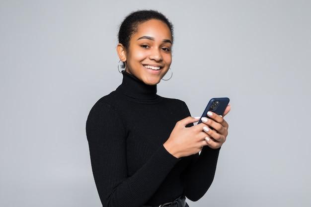 La giovane donna latina ha letto qualcosa sul cellulare isolato