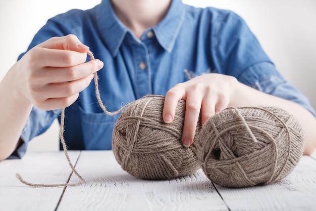 La giovane donna lavora all'uncinetto una coperta calda con lana beige