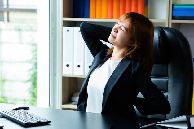 La giovane donna lavoratrice sente il mal di schiena all'ufficio