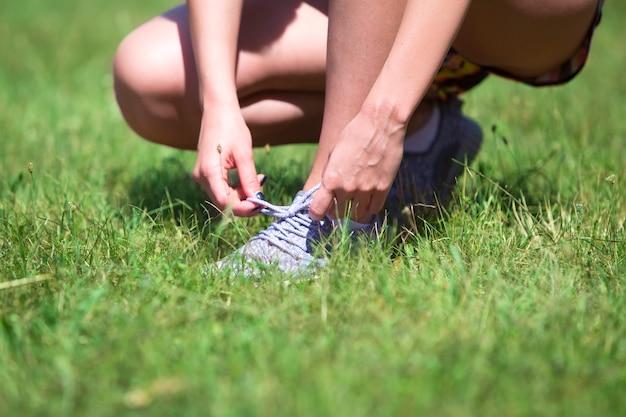 La giovane donna lega i suoi lacci delle scarpe da ginnastica