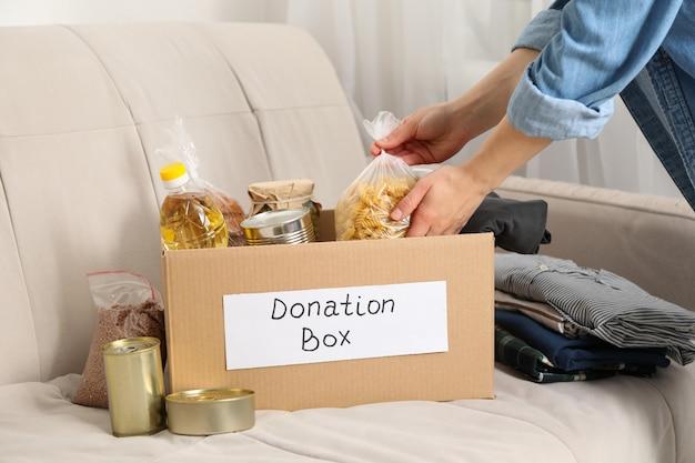 La giovane donna mette i generi alimentari nella scatola di donazione