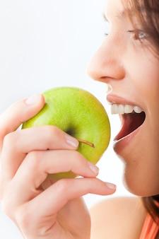 La giovane donna morde in una mela fresca e sana