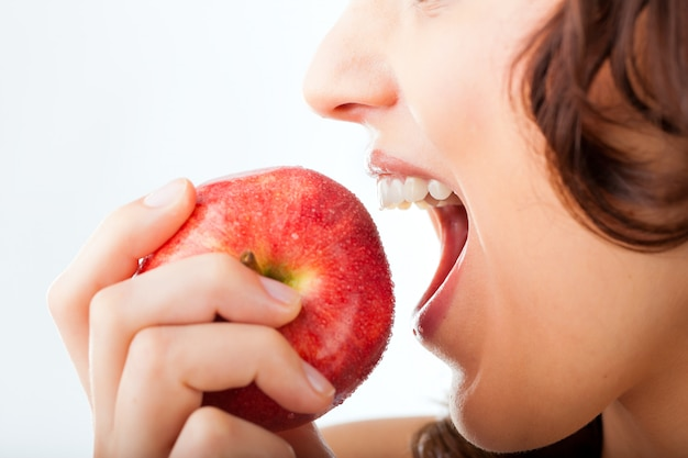 La giovane donna morde in una mela