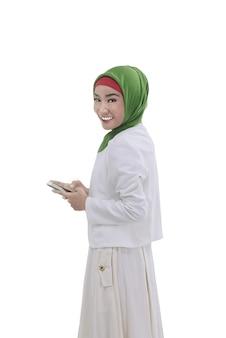 La giovane donna musulmana asiatica tiene il telefono a disposizione