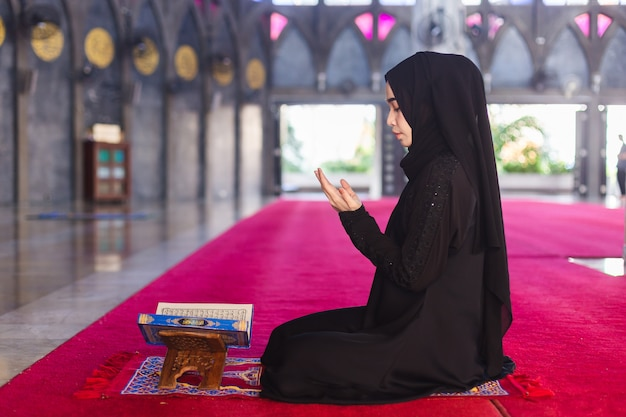 La giovane donna musulmana in vestito nero da usura ha letto il corano e fa il desiderio pregare nella moschea. esprimi un desiderio e leggi il corano in ramadan.