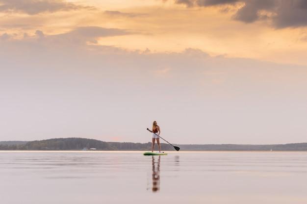 La giovane donna nel mare si alza sulla tavola di sup della pagaia con i bei colori del tramonto o dell'alba