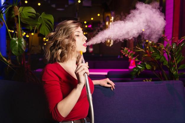La giovane donna nel vestito rosso fuma un hookan. il night club o il bar shisha fumante.